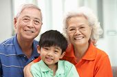 Portrait Of Chinese Grandparents With Grandson Relaxing At Home Together