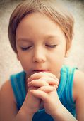 Color photo of a young boy who is praying