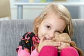 Cute little girl smiling impishly on sofa, hugging soft toy.