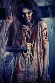 Bloodthirsty zombi with a knife standing at the night cemetery in the mist and moonlight.