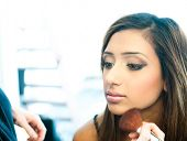 Attractive young asian indian woman having her make up done by a make up artist