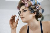 Closeup of a beautiful model in hair curlers using eyelash curler