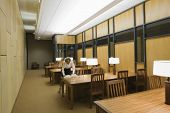 Woman reading book in an empty reading room at library