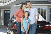 Portrait of a happy couple with daughter standing against car and house