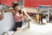Beautiful young woman with milkshake at the diner table