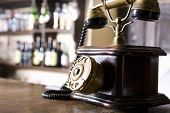 stock photo of rotary dial telephone  - Closeup of a wood and brass antique dial telephone on bar counter - JPG