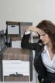 Stressed businesswoman and moving boxes at office desk