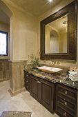 Unidad de baño marrón oscuro con marco de espejo de cuero