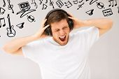 music and technology - young man with headphones listening loud music