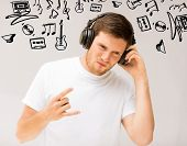 music and technology - young man with headphones listening rock music