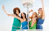 summer holidays and vacation concept - girls waving on boat or yacht