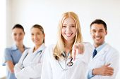 healthcare and medical concept - attractive female doctor in front of medical group
