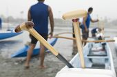 Wooden oars on outrigger canoe with canoeists in background at beach