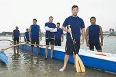 Group portrait of multiethnic outrigger canoeing team on beach