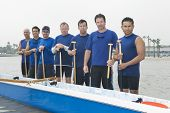 Group portrait of multiethnic outrigger canoeing team