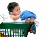 stock photo of baby-boy  - Baby boy in a laundry basket determined to get those potty pants on himself - JPG