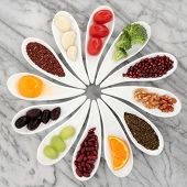 Healthy super food selection in white  porcelain dishes over marble background.