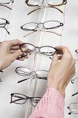 Closeup of a woman's hands choosing eyeglasses from rack