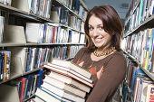 Estudiante de la Universidad de la mujer sosteniendo libros en retrato de biblioteca