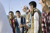 Smiling male members of three generation family holding fishing rods outdoors