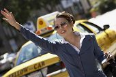 picture of cabs  - Asian businesswoman hailing cab while using cellphone with hands free device - JPG
