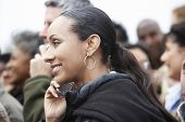Closeup side view of an African American woman using cellphone in blurred crowd