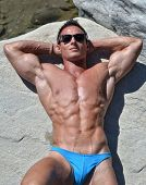 Fit And Athletic Young Bodybuilder Resting And Sunbathing On Rock