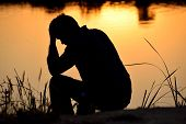 stock photo of sadness  - depressed man sitting against the light reflected in the water - JPG