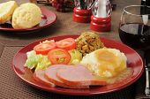 stock photo of biscuits gravy  - Ham dinner with cornbread stuffing mashed potatoes and gravy - JPG