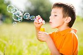 Young caucasian boy blowing the soap bubbles