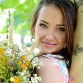 young beautiful lady with field flowers outdoor portrait, charming girl resting in summer park