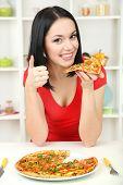 Menina com uma deliciosa pizza no fundo da cozinha