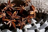 Star anise on wicker mat, on wooden background