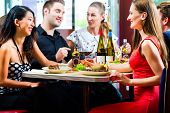 stock photo of diners  - Friends or couples eating fast food and drinking beer and wine in a American fast food diner - JPG