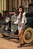 stock photo of mini-skirt  - Smoking woman in mini skirt and high heels near old car - JPG