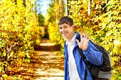 picture of goodbye  - young man wave goodbye in the autumn park avenue - JPG