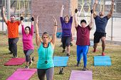 pic of boot camp  - Mature adult boot camp fitness class stretching outdoors - JPG