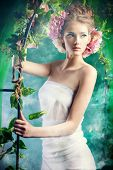 stock photo of arch  - Beautiful young woman standing under an arch of flowers and overgrown loach - JPG