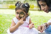 Daughter at outdoor green park with mother. Cute Indian girl peeking through magnifying glass with p