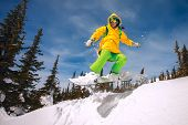 stock photo of snowboarding  - Snowboarder jumping through air with deep blue sky in background - JPG