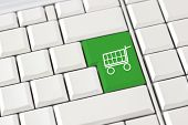 stock photo of trolley  - Green shopping trolley icon on a computer keyboard conceptual of e - JPG
