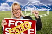 Very Happy Woman with Sold For Sale Real Estate Sign, Keys In Hand and Ghosted House Behind Her.