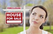 Thoughtful Pretty Mixed Race Woman In Front of Home and Foreclosure House For Sale Real Estate Sign