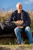image of lap  - happy senior couple relaxing together in the sunshine on a wooden bench in the countryside with the one reclining full length on the seat with his head on his partners lap - JPG