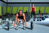 gym man and woman with weight lifting bar workout in crossfit exercise
