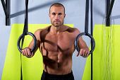 Crossfit dip ring man relaxed after workout at gym dipping exercise