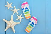 Starfish sea shells and rainbow coloured flip flops over wooden blue background.