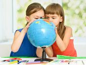 Little girls are examining globe while sitting at table