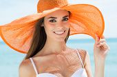 Portrait Of Smiling Girl In Orange Hat At Beach
