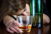 Drunk woman suffering from a hangover and holding a glass of liquor